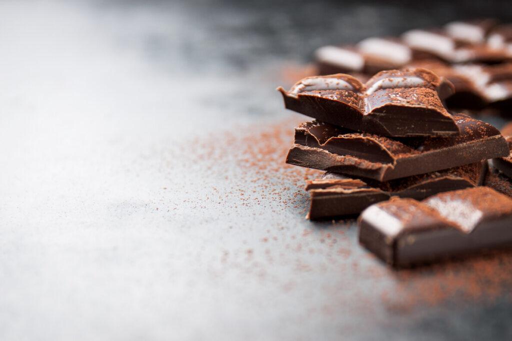 кусочки шоколада на деревянном столе и посыпанные какао